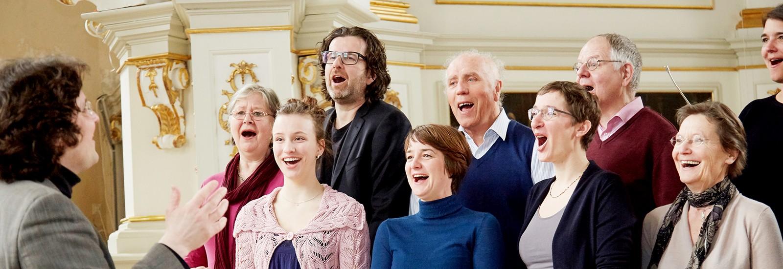 Sängerinnen und Sänger und Dirigent